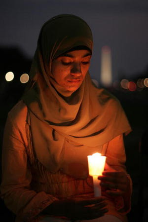 In 2005, a Muslim woman holds a candle at a 9/11 remembrance vigil in Washington, DC.  Win McNamee/Getty Images