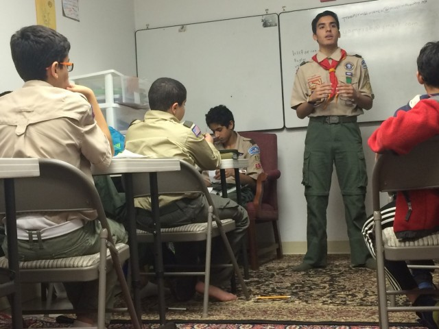"""Yousof Omeish, 15, the leader of Boy Scout Troop 114, talks to members at their weekly meeting."""