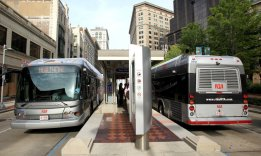 Euclid Avenue Buses and Stations with one car lane beside each